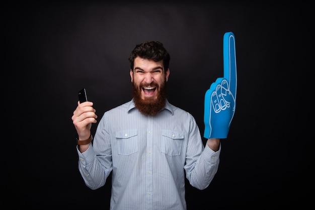 내가이 겄어! 가자 팀! 멋진 팬, 수염 난 남자가 휴대전화를 들고 검정색 배경에 팬 장갑 nr 1을 들고 있습니다.