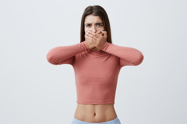 I won't say anything. portrait of handsome charming young caucasian girl with brown long hair in pink top and blue trousers clothing mouth with both hands in frightened look. body language.