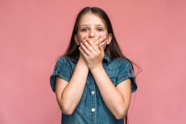 わからない!秘密を言うのを恐れて、手で口を覆っている怖い少女の肖像画。子供は話すのが怖かった。ピンクの背景に分離された屋内スタジオショット