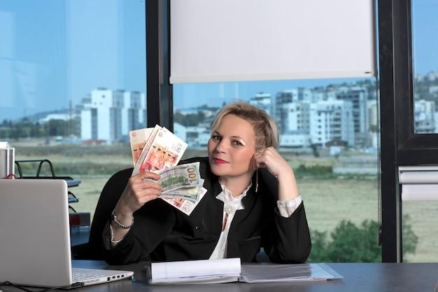 勝った!オフィスのテーブルに座っているお金の紙幣の束の後ろに隠れているビジネススーツのきれいな女性を考えています。手にドルと英国ポンドのスターリング紙幣を持つ金髪のビジネスレディ