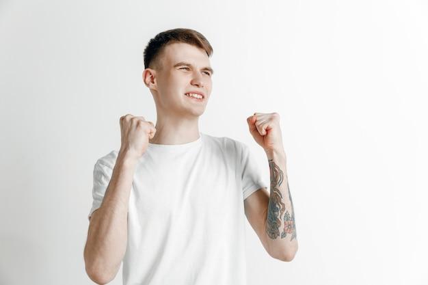 勝った。勝者であることを祝う勝利の成功幸せな男。灰色のスタジオの背景に白人男性モデルの動的画像。勝利、喜びの概念。人間の顔の感情の概念。