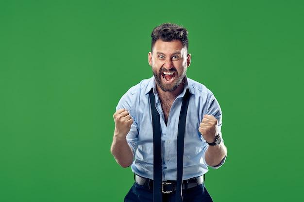 Я выиграл. добиваясь успеха счастливый человек празднует быть победителем. динамическое изображение кавказской мужской модели на зеленом. победа, концепция восторга