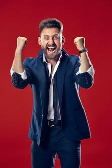 Ho vinto. uomo felice di successo vincente che celebra essere un vincitore. immagine dinamica del modello maschio caucasico su sfondo rosso studio. vittoria, concetto di gioia