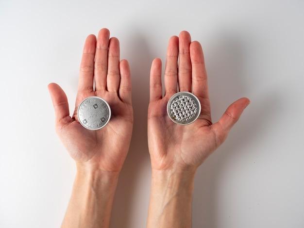 I10.03.2021ロシア、モスクワ。彼の手には、ネスプレッソコーヒーを挽いた2つのアルミニウムカプセルがあります。それらの1つが使用されます。白い背景、上面図、フラットレイ。使用済みアイテムのリサイクルの概念