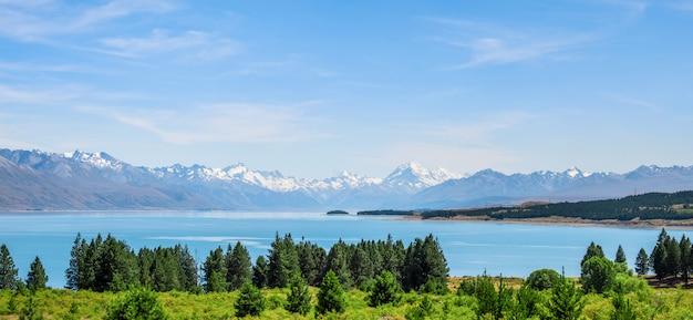 緑の木と青い空と湖の横にある夏のマウントクックの美しいシーンのパノラマビュー。ニュージーランドi