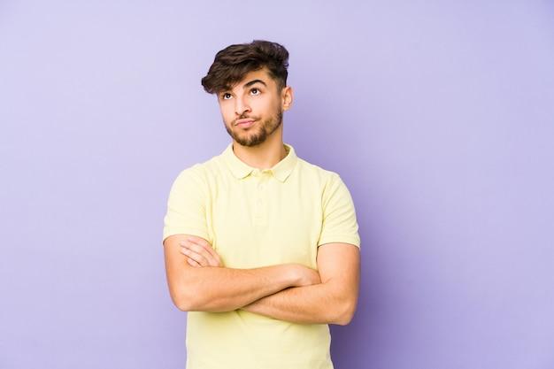 皮肉な表情でカメラで見ている不幸な紫色の壁に若いian男。