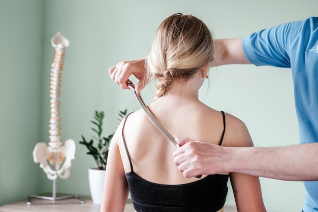 Iastm treatment, girl receiving soft tissue treatment on her neck with stainless steel tool, soft tissue mobilization