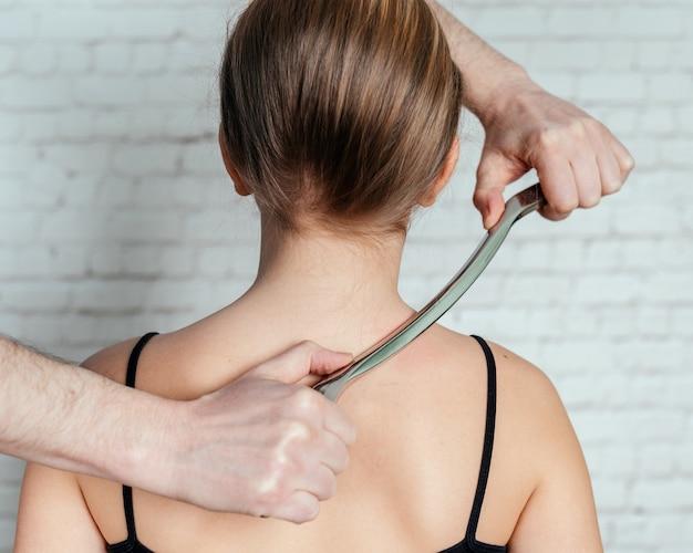 Процедура iastm, девушка получает лечение мягких тканей шеи с помощью инструмента из нержавеющей стали, мобилизация мягких тканей