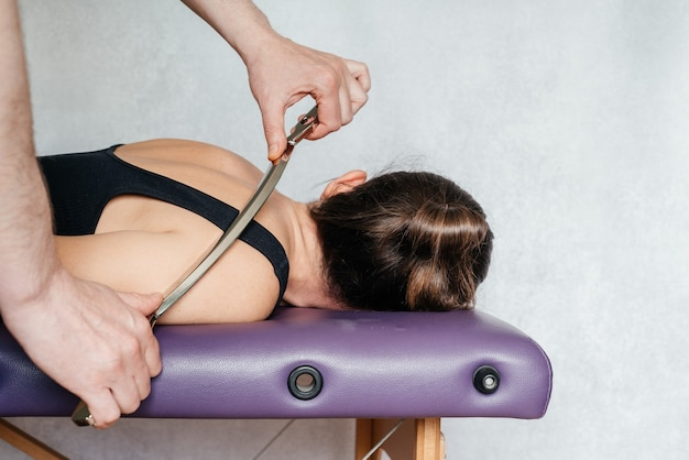 Iastm treatment for myofascial restriction a woman receiving soft tissue treatment on her neck with ...