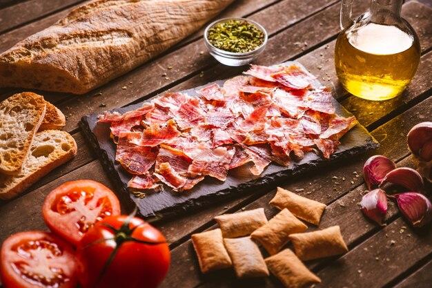 갈색 나무 테이블에 있는 슬레이트 접시에 이베리아 햄을 자르고 그 주위에 몇 가지 재료를 얹었다