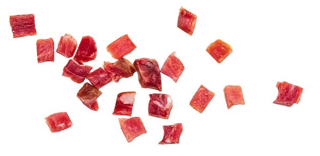 Иберийскую ветчину (серрано) нарезать кубиками (нарезать кубиками). изолированные на белом фоне.