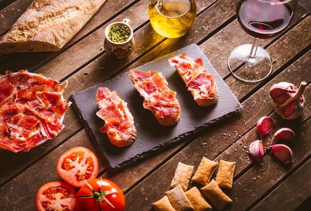 갈색 나무 테이블에 있는 슬레이트 접시에 이베리아 햄 토스트