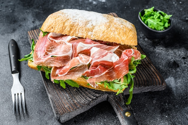 Iberico jamon ham sandwich on ciabatta bread. black table. top view.