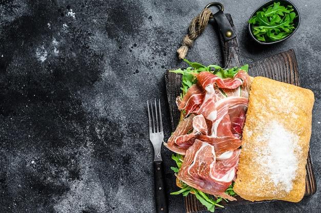 Бутерброд с ветчиной иберико с хамоном на хлебе чиабатта. черный стол. вид сверху. скопируйте пространство.