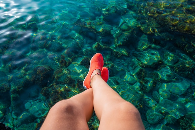 Ibiza girl legs at portinatx beach clear water