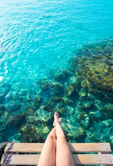 Ibiza girl legs at portinatx beach clear water