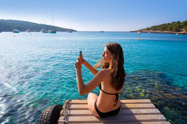 Ibiza girl taking smartphone photos