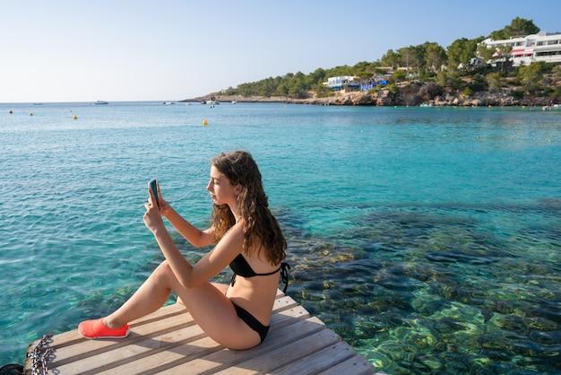 Ibiza girl taking smartphone photos