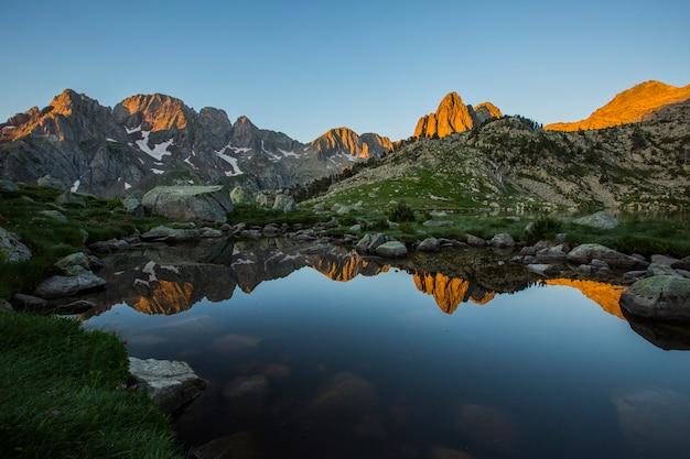 Восход солнца в ibon grande de batisielles, природный парк посец маладета, испания