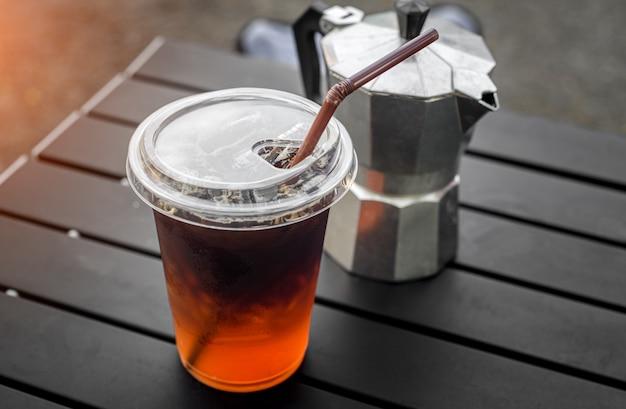 屋外照明付きのアジアンスタイルのストリートカフェからのプラスチックガラスのアイスアメリカーノコーヒー。
