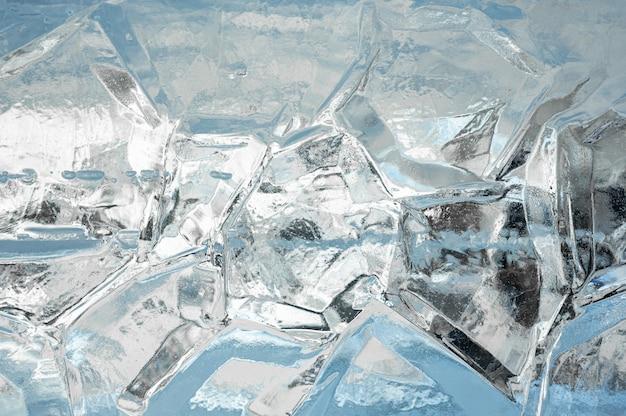 Ледяной фон полный кадр текстур, образованных блоком треснувшего льда, на голубом фоне.