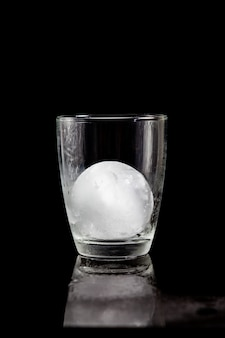 Ice ball inside cocktail glass on a reflective black table.