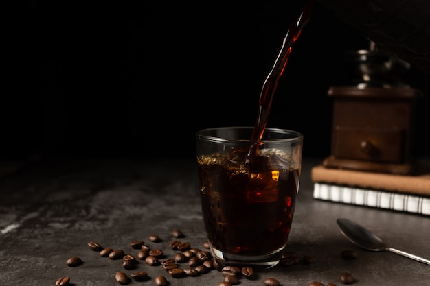 Ice black coffee in a glass on the wooden table.