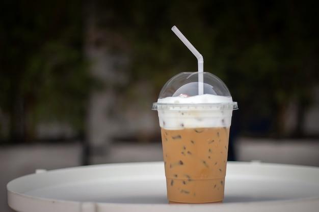 白いテーブルの上のプラスチックカップの氷カプチーノ