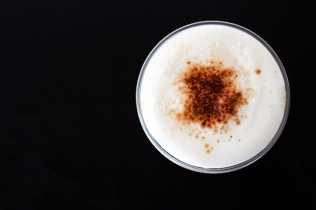 Ice cappuccino. top view of milk foam and cinnamon powder topping. refreshment beverage.