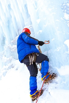 Ice climber checks the reliability of the anchor with ice screw before climbing