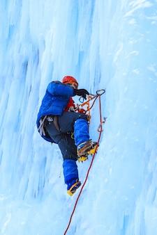 Ice climber climbs a vertical blue ice wall during a snowfall