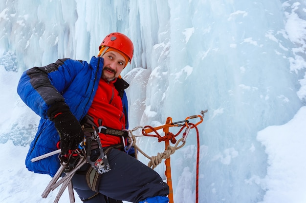 Ice climber is fixed on the vertical surface of the glacier with safety anchor