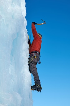 Ice-climber man with ice tools axe climbing a large wall of ice.