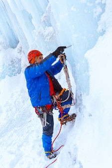 Ice climber preraring running belay screwing ice screw into glacier surface