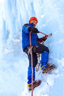 Ice climber stretches a safety rope standing on the vertical wall of the glacier