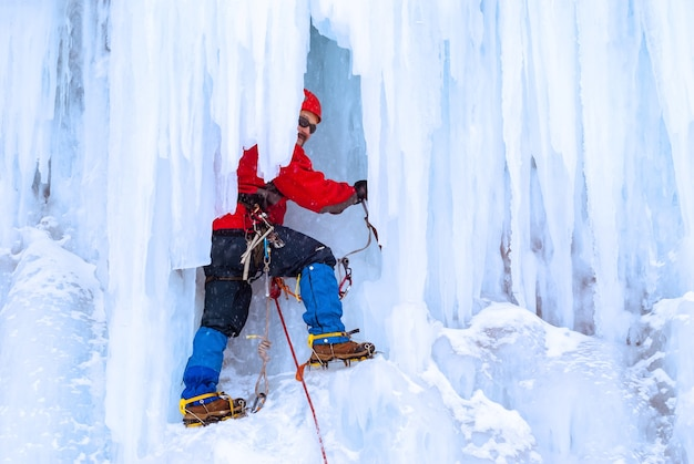 Ice climber on a vertical wall of a frozen waterfall among huge icicles
