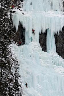 凍った滝、レイクルイーズ、バンフ国立公園、アルバータ、カナダのアイスクライマー