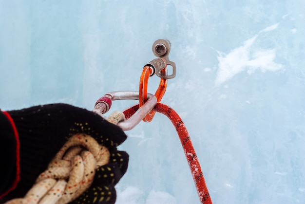 Ice climbing anchor with ice screw safety rope carabiners and climber arm closeup