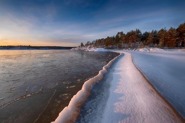 夜明けにラドガ湖の水の氷の海岸