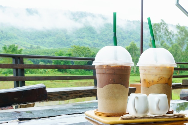 Ice cocoa and ice milk tea on the table with mountain scenery and mist in rainny day