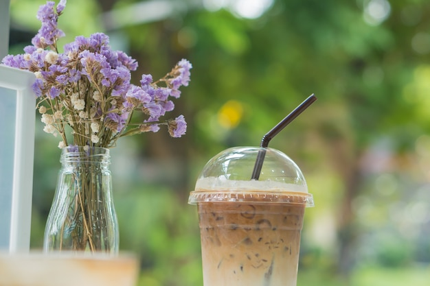 Ice coffee in clear plastic with dry flowers on table cafe