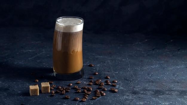 背の高いグラスにアイスコーヒーフラッペ。低いキーで暗い背景に涼しい夏の飲み物。牛乳の流れがコーヒーに注ぐ。