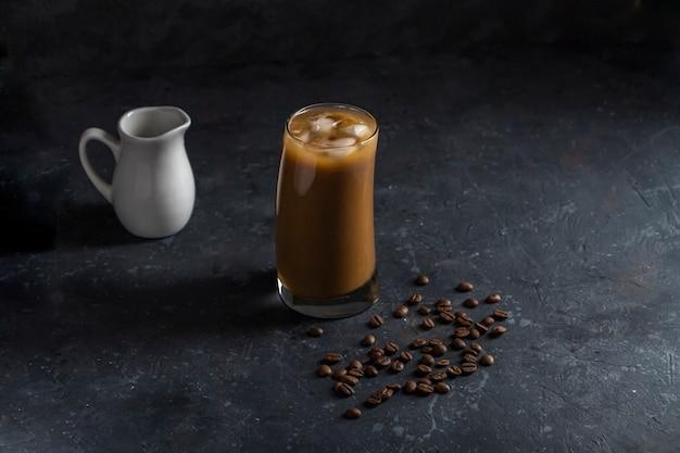 背の高いグラスにアイスコーヒーフラッペ。低いキーで暗い背景に涼しい夏の飲み物。