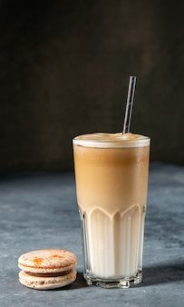 Ice coffee in a  glass with milk poured over and macaron on a old rustic grey table cold summer drink latte