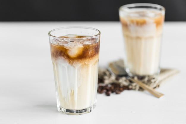 Ледяной кофе в стакане со сливками и кофейные зерна на столе
