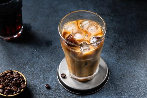 クリームを注いだ背の高いグラスにアイスコーヒー。アーモンドミルクラテ。冷たい夏の飲み物。ガラスのコールドブリュー。ガラスのベジタリアンコーヒー。ベトナムアイスコーヒー。ビーガンラテ