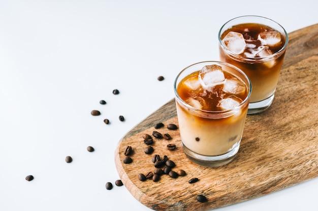 Ледяной кофе в стакане с молоком и кубиками льда, кофейные зерна на белом столе