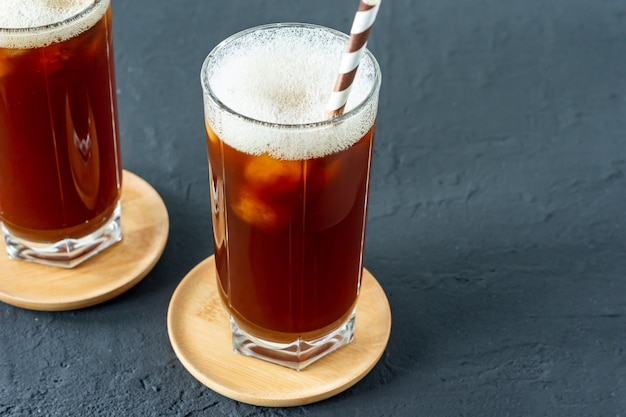 黒いコンクリートの背景に氷と背の高いグラスでアイスコーヒー。紙ストローで寒い夏の飲み物。