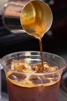 アイスコーヒーの準備準備サービスのコンセプト。バリスタ。コーヒーショップでエスプレッソを作ります。閉じる。挽きたてのコーヒーがクローズアップ。縦の写真