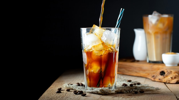 Ice coffee in a tall glass with cream poured over.